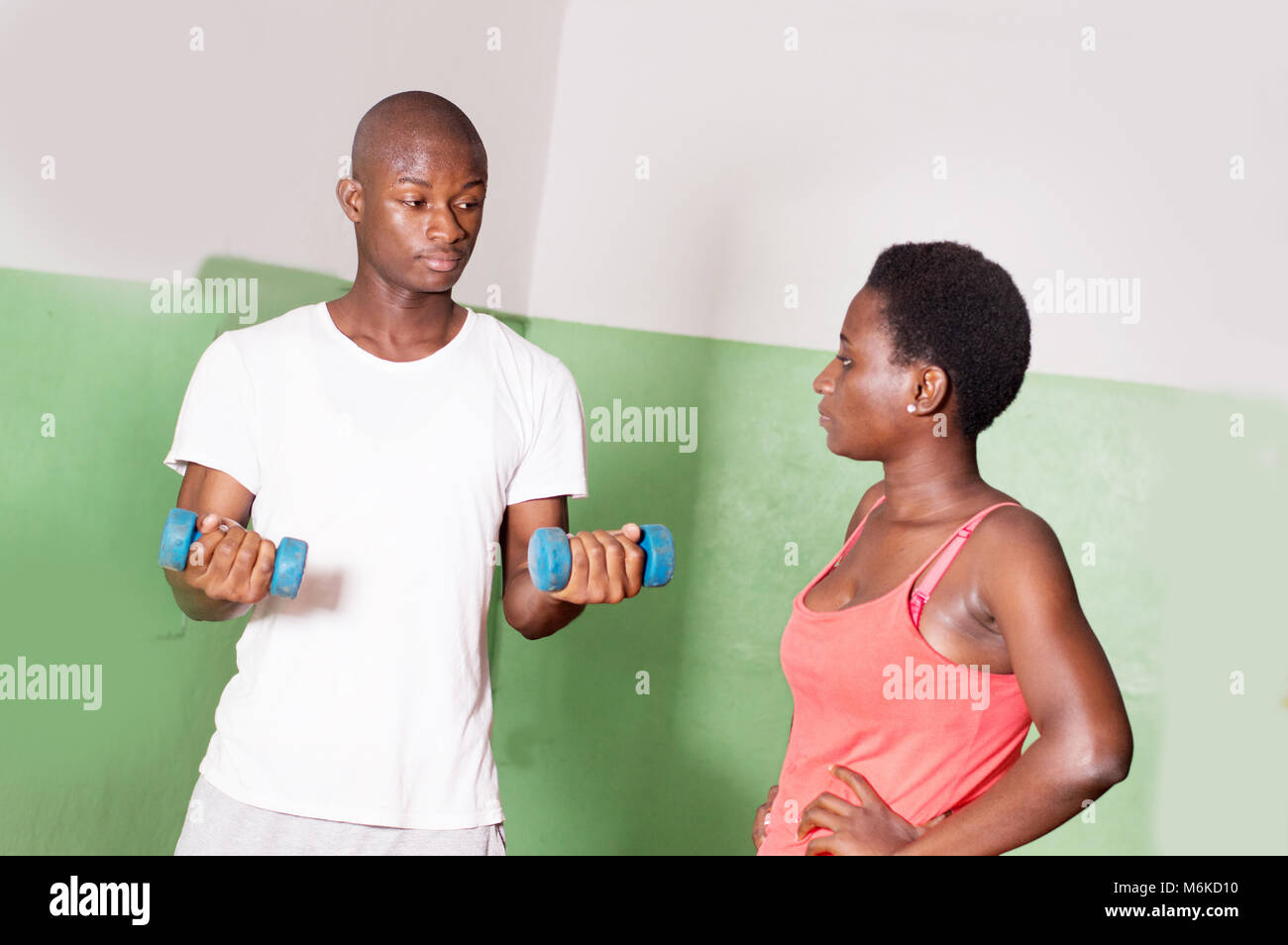 e trainer of the gym explains to the young woman the benefits of raising the weights. - Stock Image