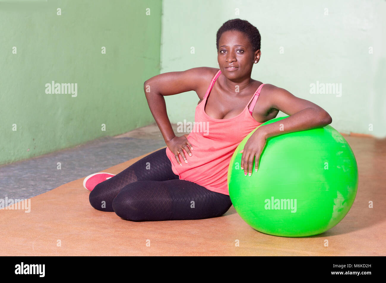 Young woman sitting on a ball for fitness. - Stock Image