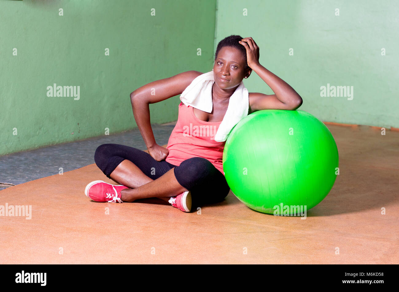 Young woman sitting and arms on a ball to do fitness exercises. - Stock Image
