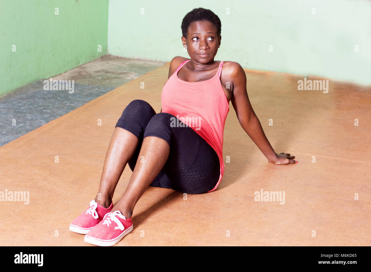 Young woman sitting in a gym while waiting for her trainer. - Stock Image