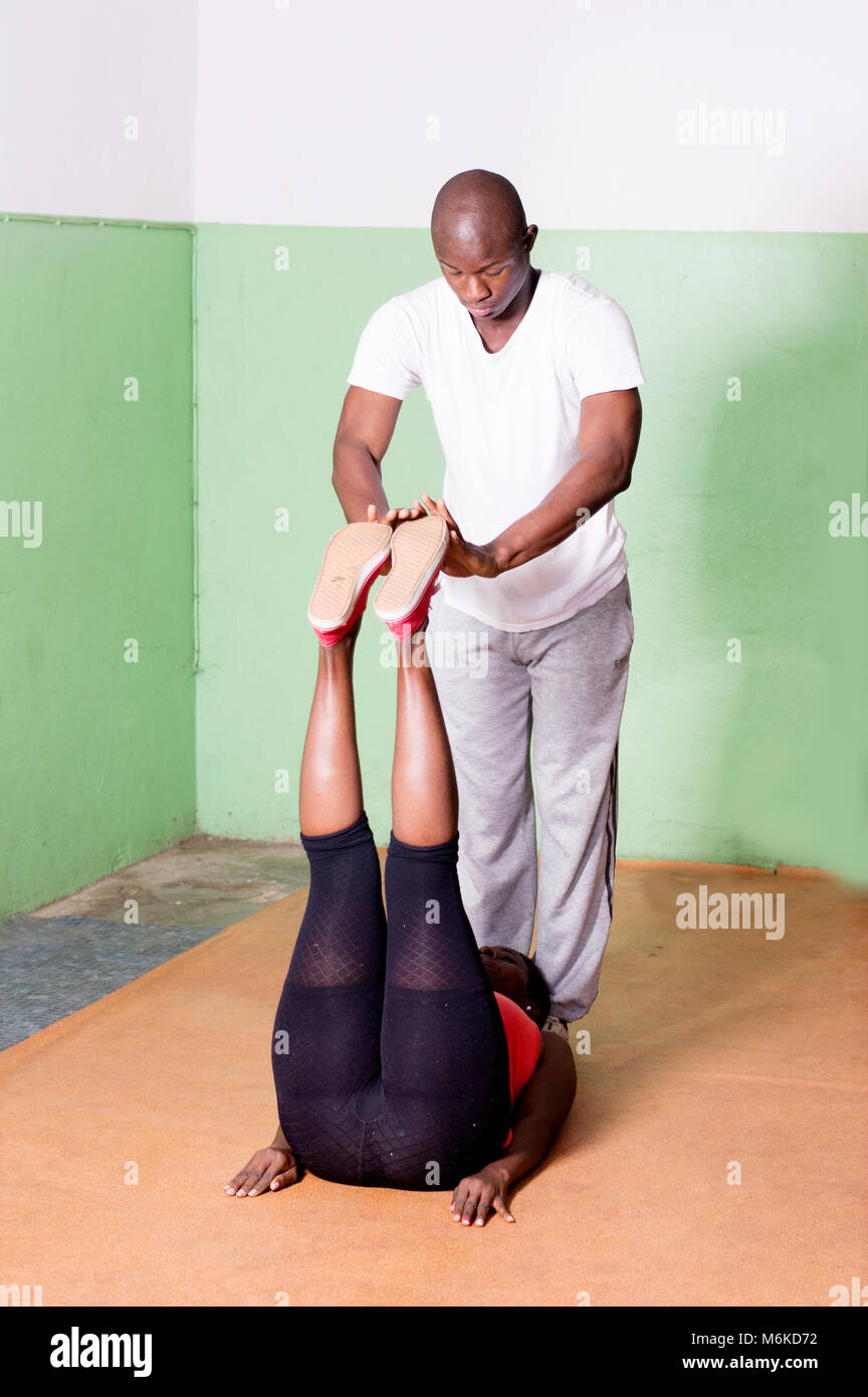 The gym coach trains the legs of the young woman lying in front of him. - Stock Image