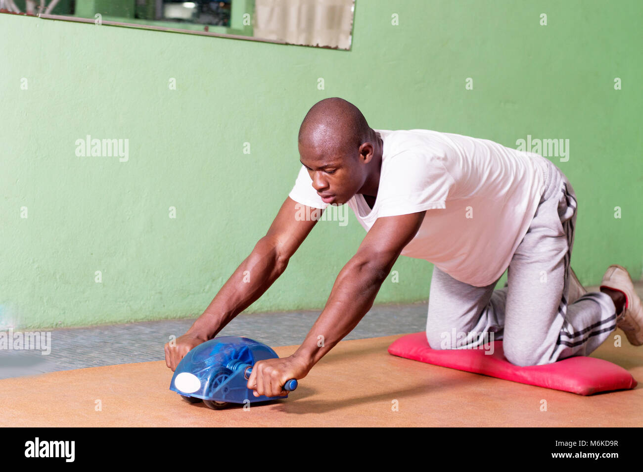 Young man doing stretching exercises on the floor in the gym. - Stock Image