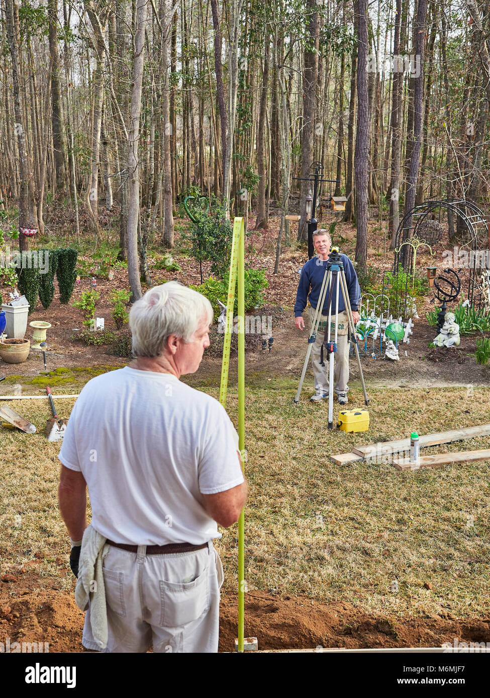 Male construction workers using a transit-level while working on a residential construction job in Pike Road Alabama, - Stock Image
