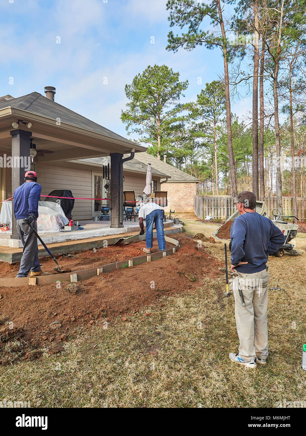 Construction workers at a residential site working on a patio for the home or house in Pike Road Alabama, USA. - Stock Image