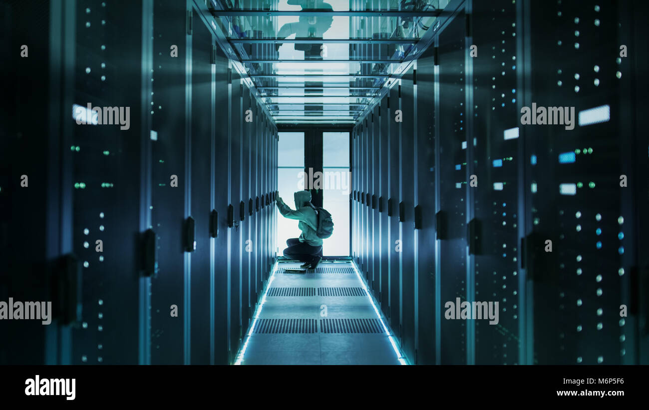 A Hooded Hacker With Laptop Connects to Rack Server and Steals Information from Corporate Data Center. - Stock Image