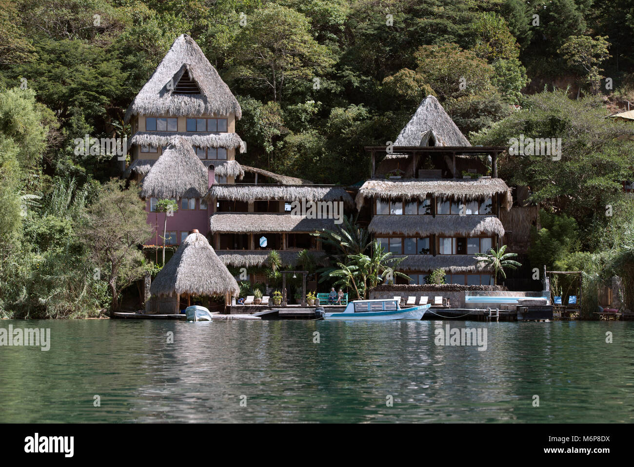 A modern hotel built in traditional Mayan style with thatched roof. Lake Atitlán, Sololá Department, Guatemala. - Stock Image