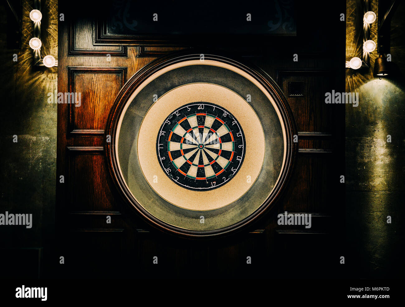 English style dart board with wooden backdrop and faded lights Stock Photo
