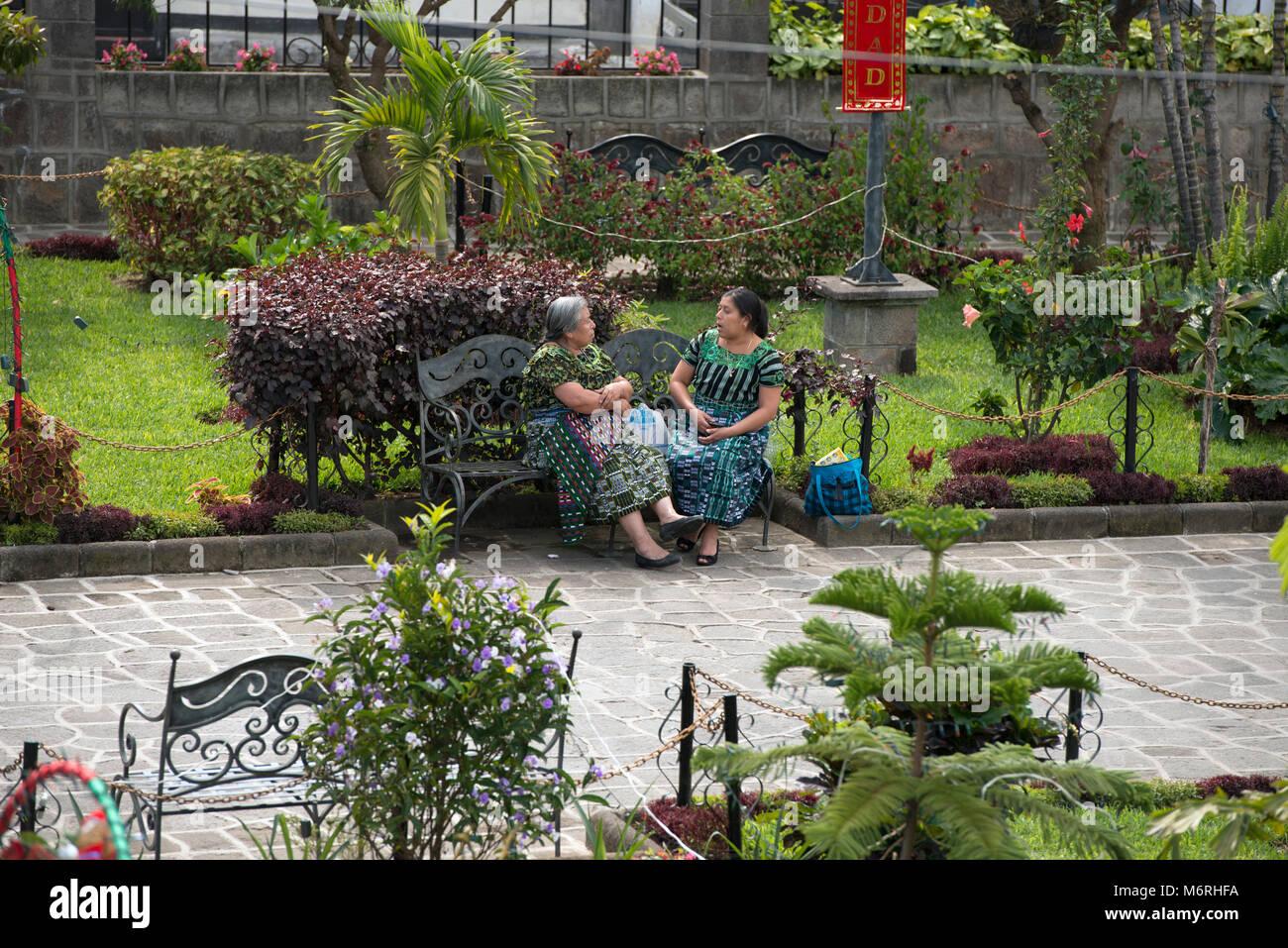 Two indigenous, ethnic Tz'utujil Maya women sitting on a park bench, talking in Santiago de Atitlán, Sololá - Stock Image