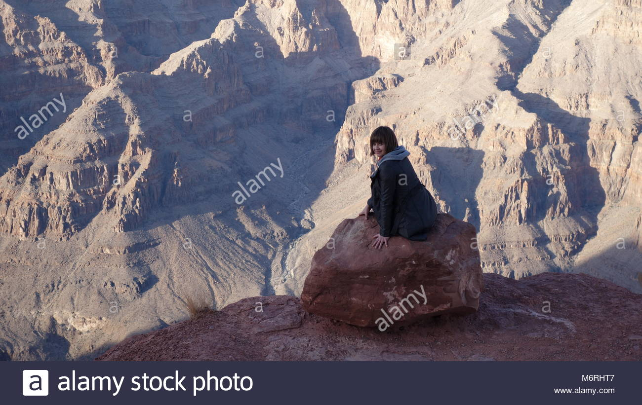 Smiling fearless girl is sitting at the edge of Grand Canyon and looking back (AZ, USA) - Stock Image