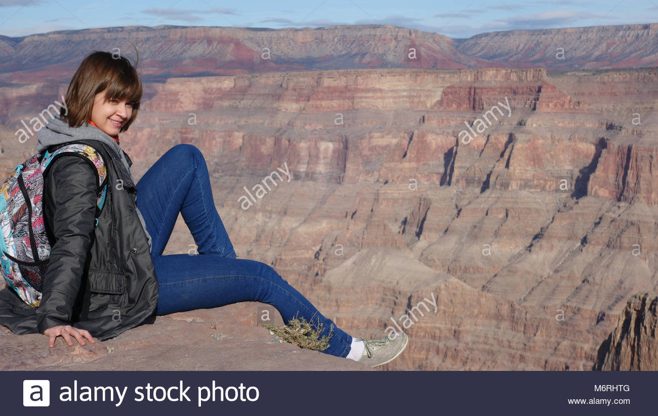 Smiling fearless girl is sitting at the edge of Grand Canyon (AZ, USA) - Stock Image