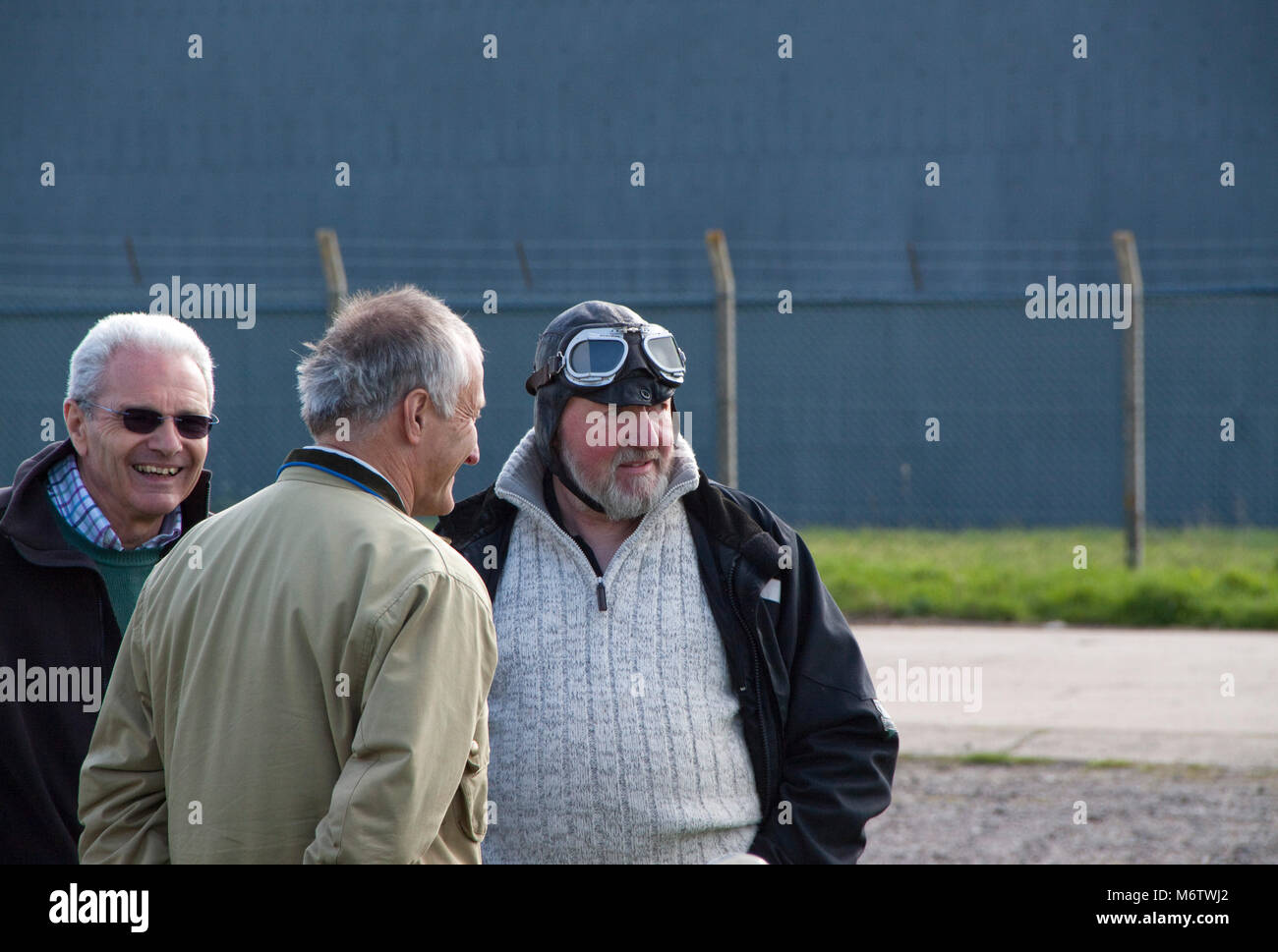 Man wearing an aviator helmet and goggles at Bugatti club meeting - Stock Image