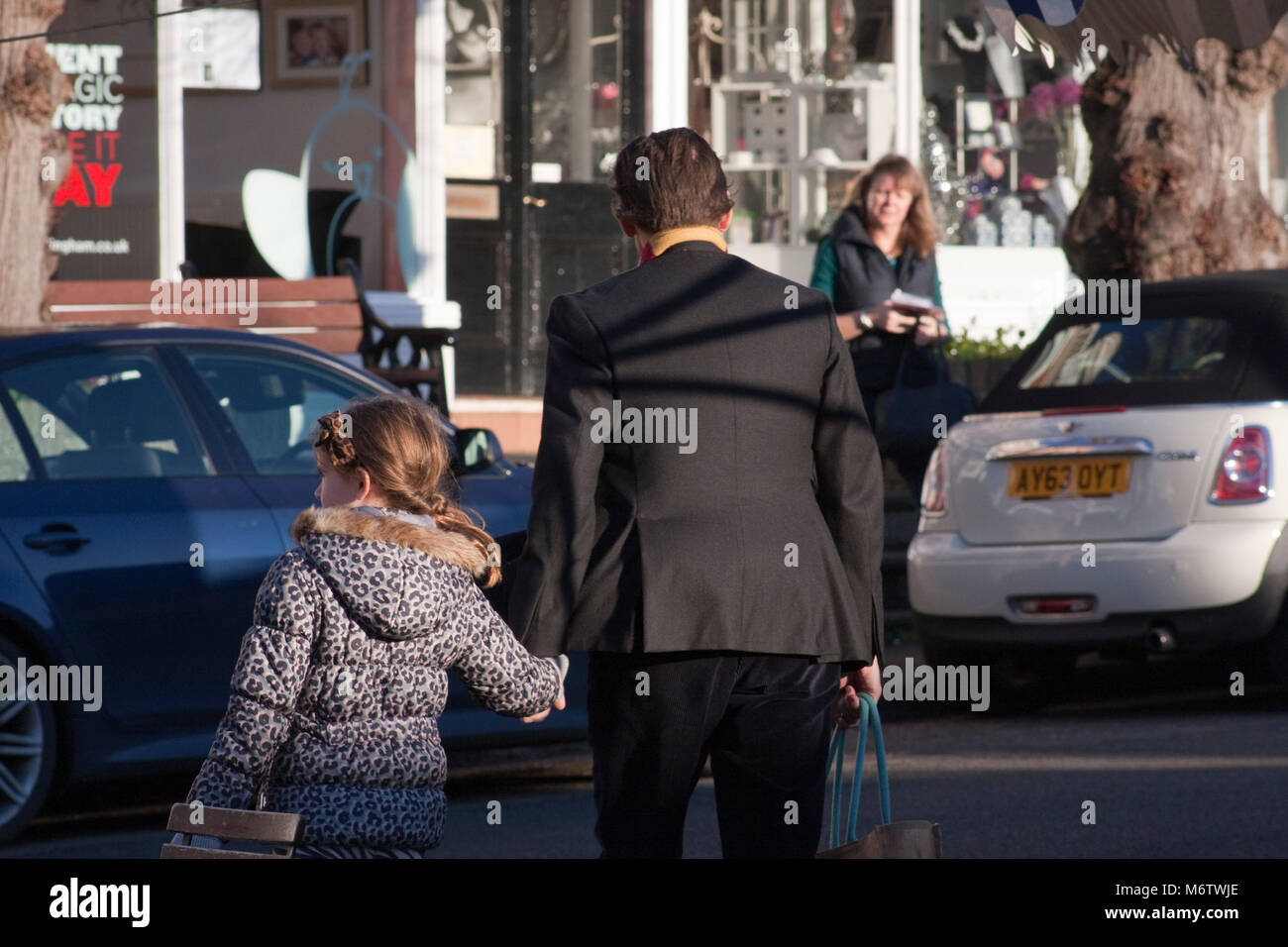 Small girl holds hands with an adult to cross the road - Stock Image