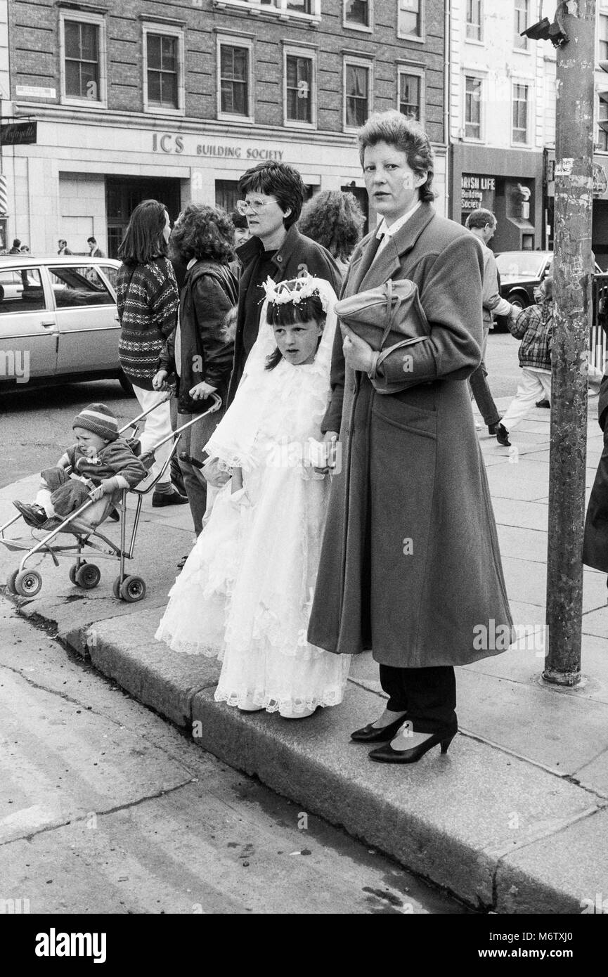 Young girl in first communion dress on street corner waiting to cross the road, Westmoreland Street, Dublin, Ireland, - Stock Image