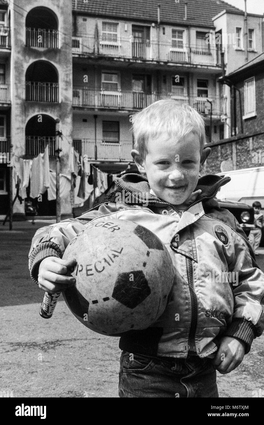 Young boy with football in courtyard of a tenement block in Dublin city center, Ireland, Archival photograph from - Stock Image