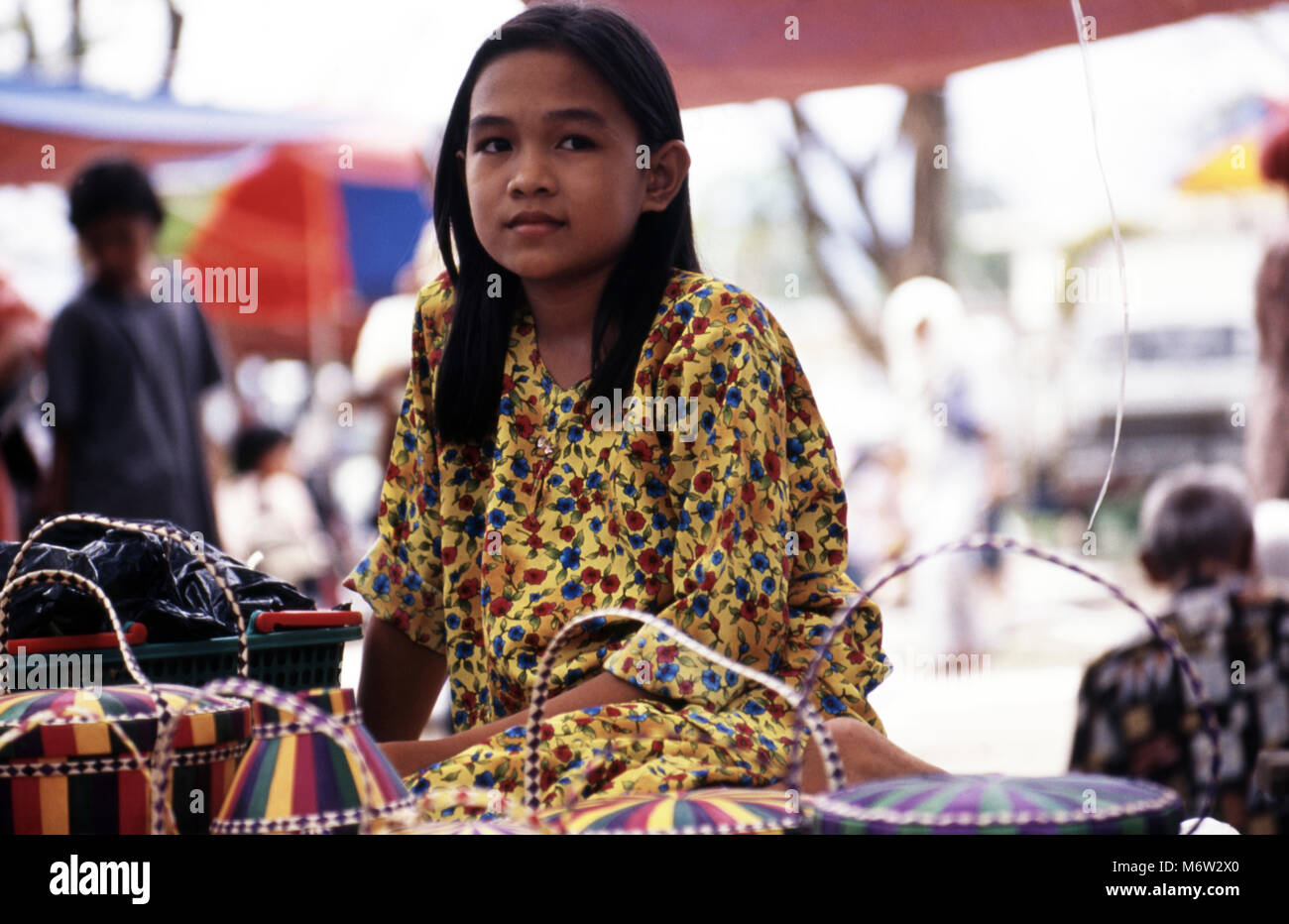 A young, indigenous, ethnic Bajau girl in a brightly coloured dress at the market in Kota Belud, Sabah, Borneo, - Stock Image