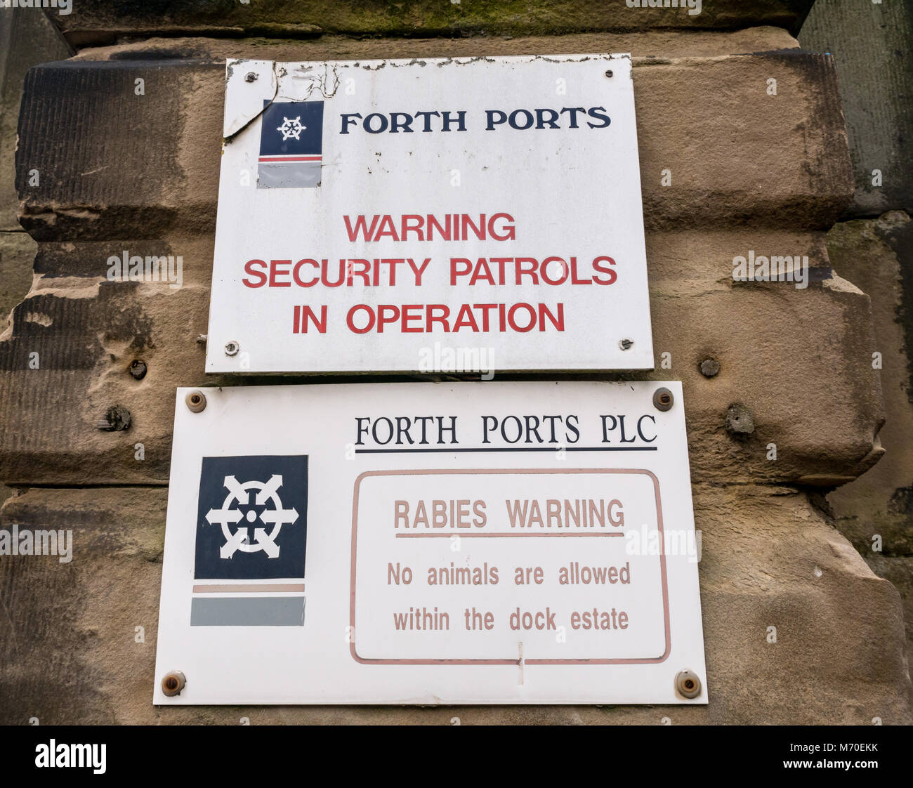 Close up of Forth Ports entrance sign warning about security patrols and rabies, Leith Dock, Edinburgh, Scotland, - Stock Image