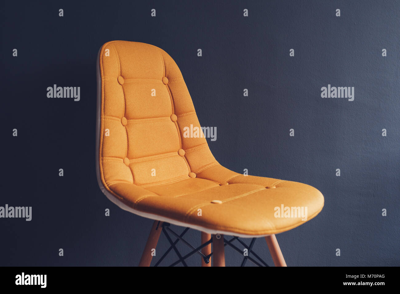Empty generic yellow chair against gray wall of waiting room interior, minimalist composition with copy space - Stock Image