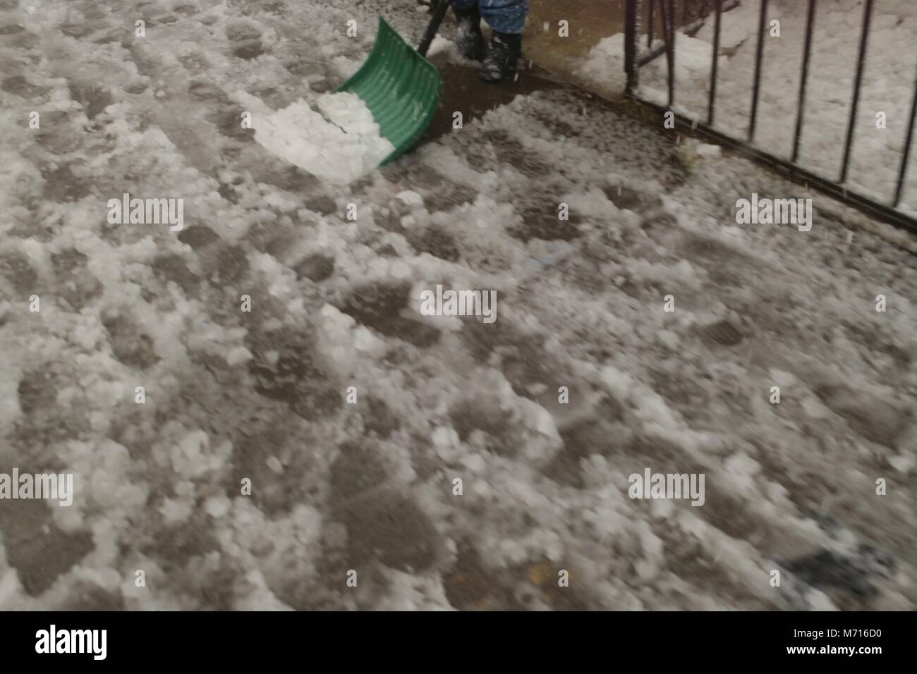 Shoveling a sidewalk covered in slushy snow during the Nor'easter of March 7th, 2018 in Brooklyn New York. - Stock Image