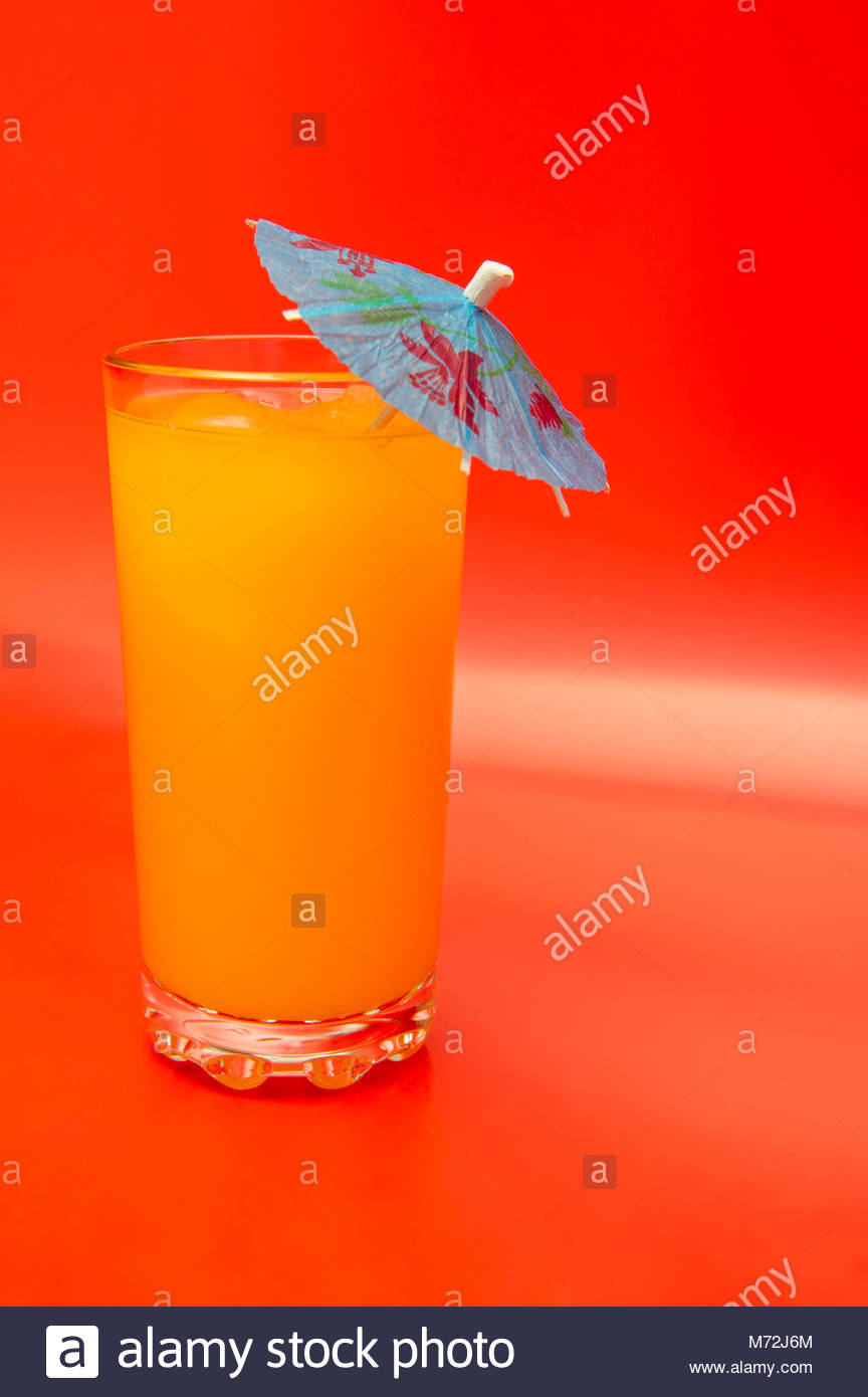 An orange drink with a mini umbrella and ice cubes on a red background - Stock Image