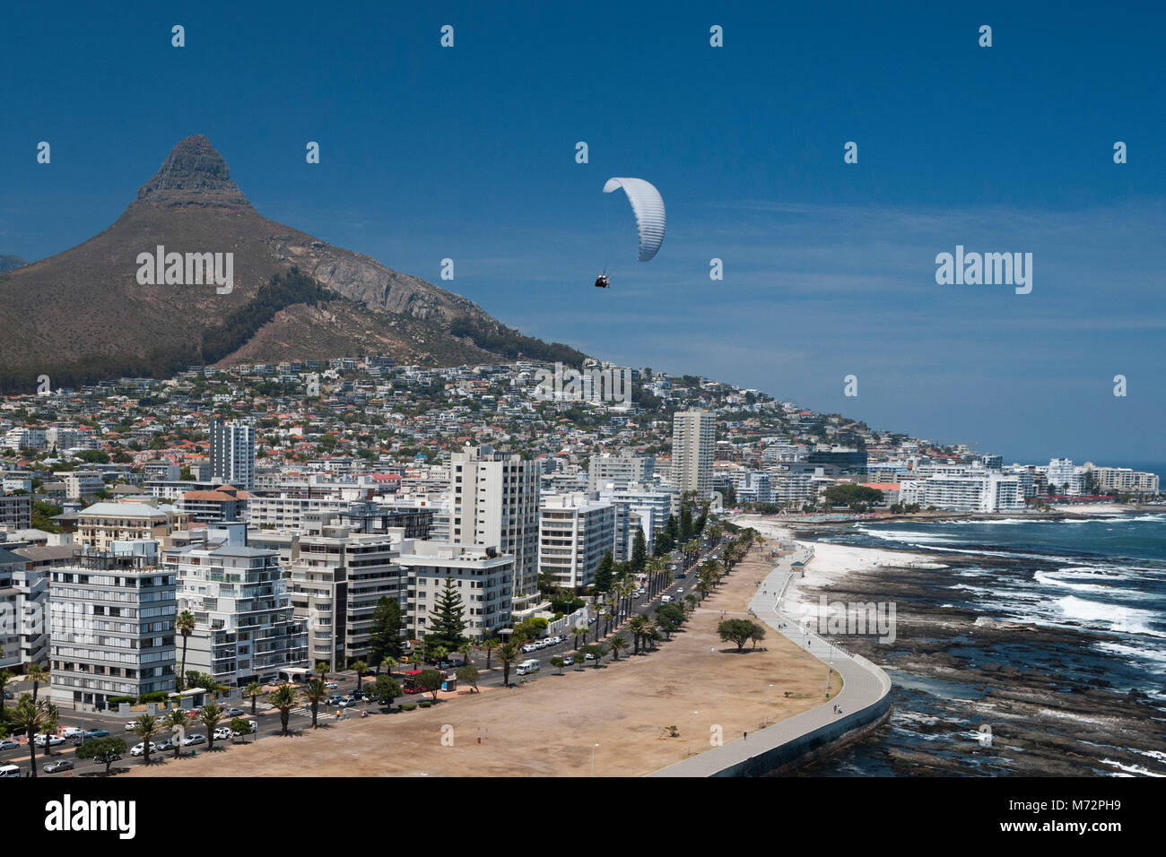 Tandem paraglider flying above Cape Town's Atlantic seaboard suburb of Sea Point with Lion's Head in the background. - Stock Image