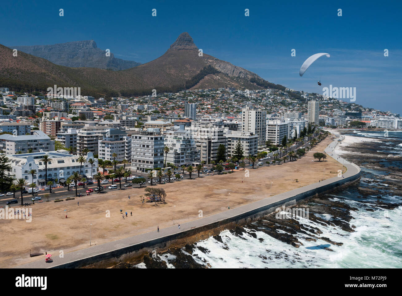 Tandem paraglider flying above Cape Town's Atlantic seaboard suburb of Sea Point with Table Mountain and Lion's - Stock Image