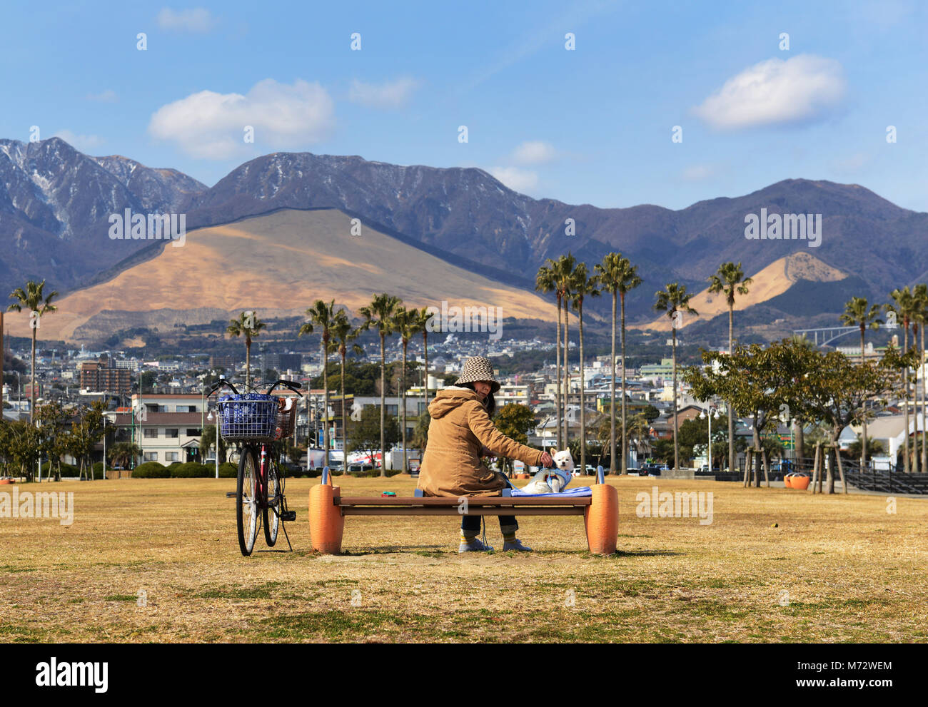 A Japanese woman with her pet dog at the Shoningahama Park in Beppu, Japan. - Stock Image