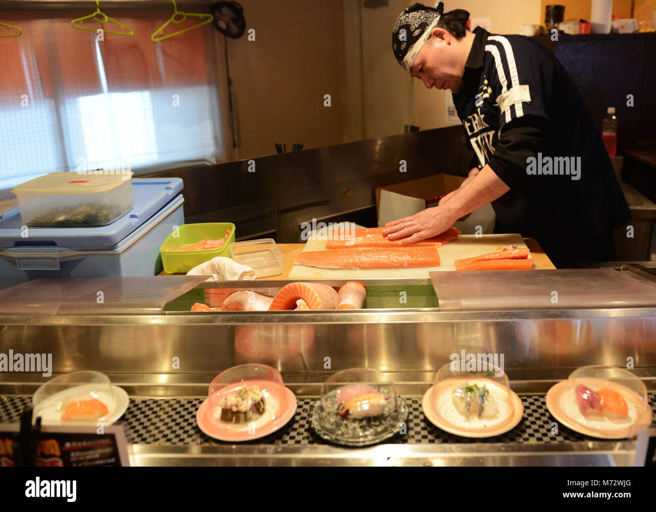 A Sushi chef cutting the fish. - Stock Image