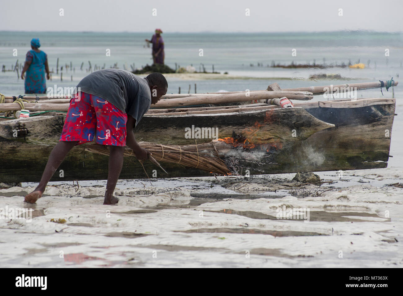 Fisherman using burning palm fronds to remove moss and green grassy growths from the side of his fishing vessel - Stock Image