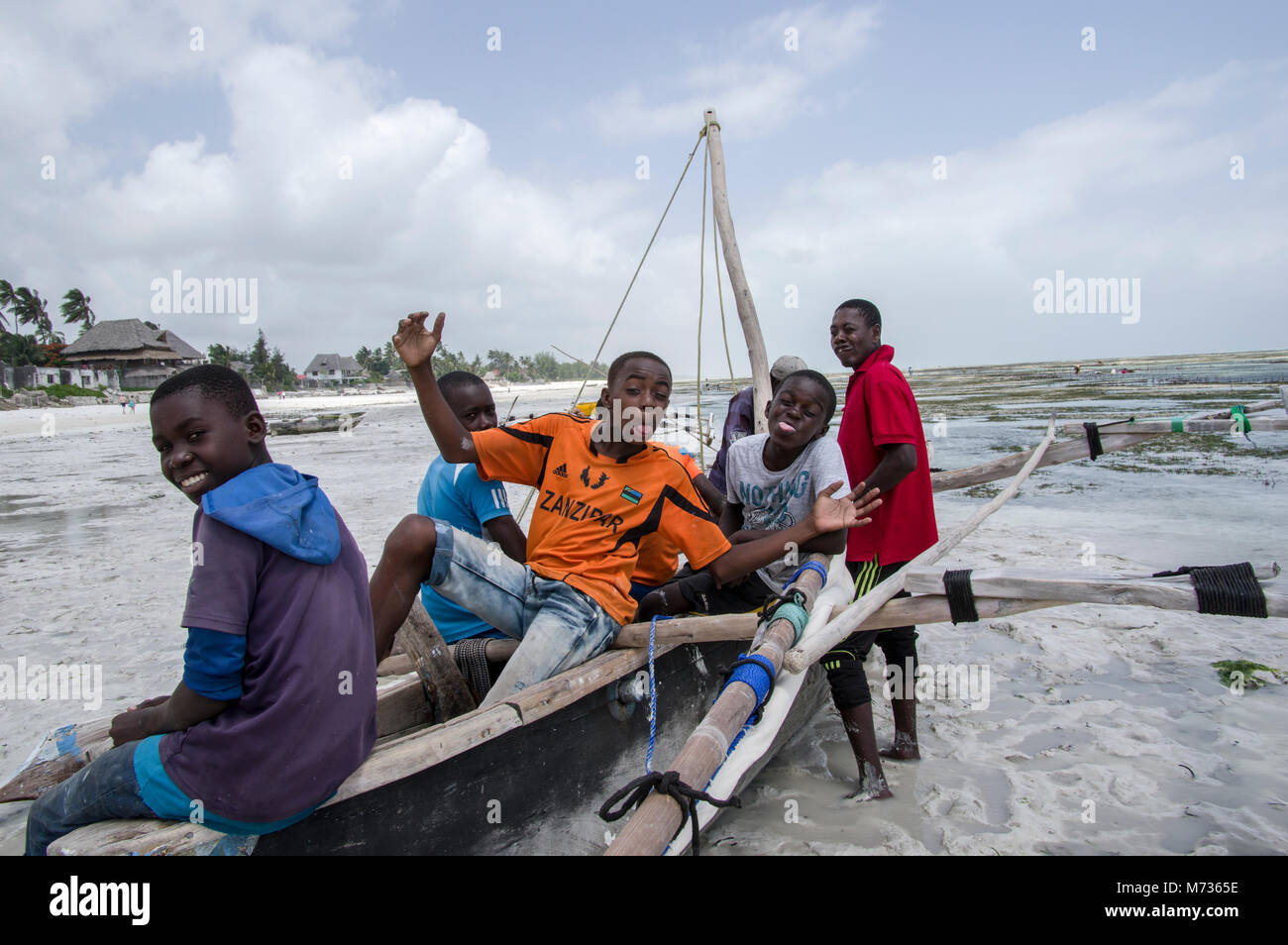six boys in jambiani beach in zanzibar making silly faces for the camera sitting on a beached dhow boat at low tide - Stock Image