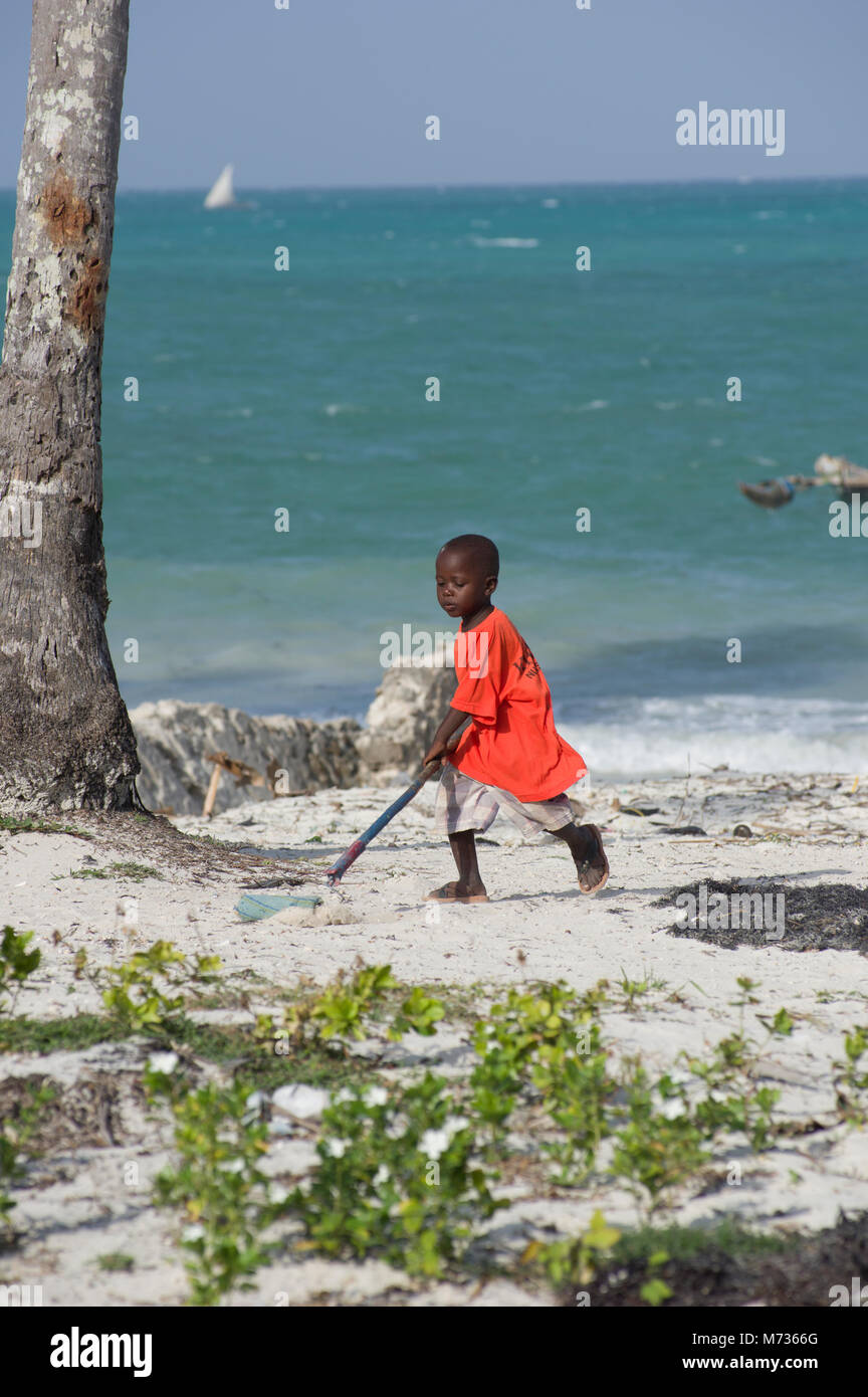a young swahili boy in red playing with a paint rollar on a long stick in the sand on jambiani beach in zanzibar - Stock Image