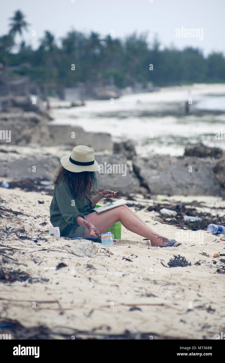 A Western woman on the beach in Jambiani Znzibar her face hidden by a straw hat sits in the sand in the sun - Stock Image