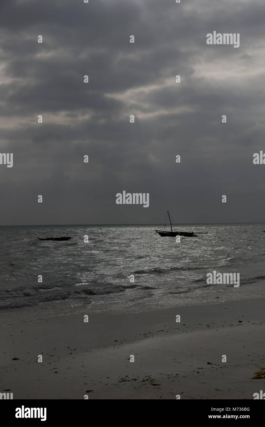 moody stormy lighting on the indian ocean in jambiani zanzibar tanzania with two dhow fishing boats on the mirrored - Stock Image