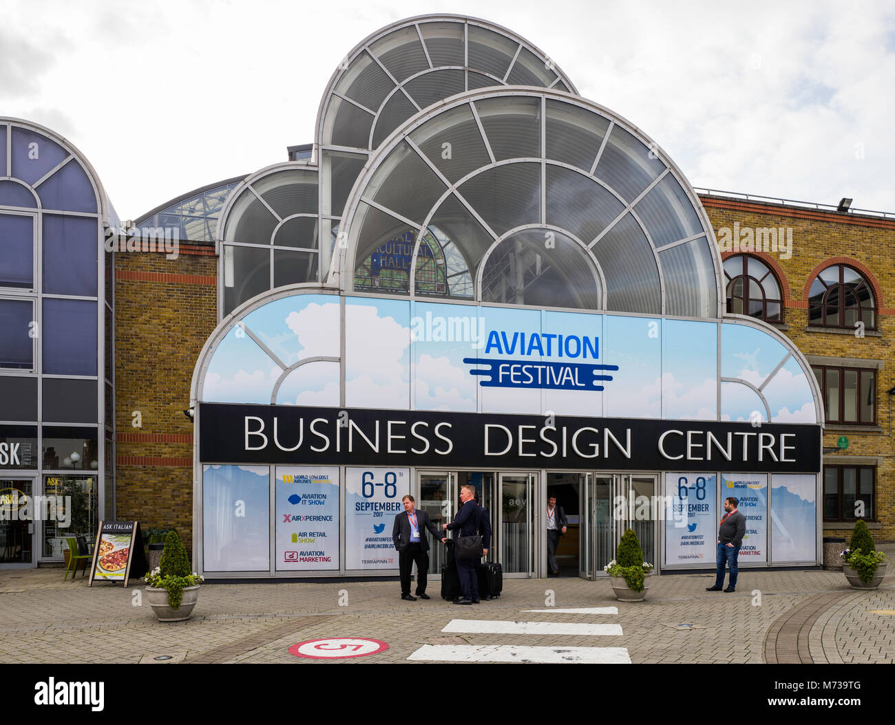 Businessmen await their taxi outside the 'Aviation Festival's at London's Business Design Centre in - Stock Image