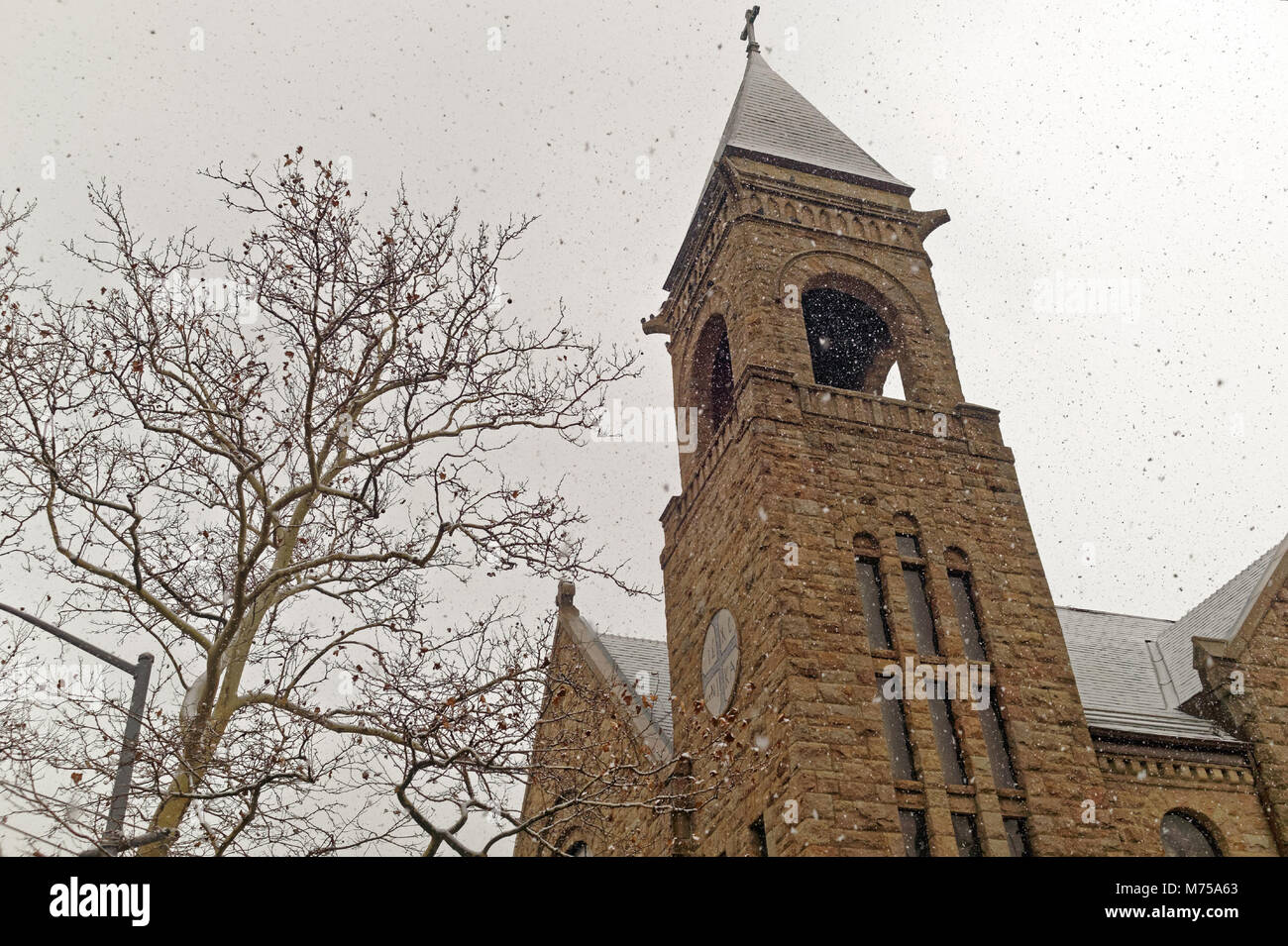 Stone church steeple in Brooklyn, New York during a light snowfall. - Stock Image