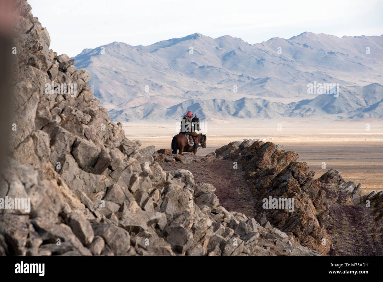 A Kazakh nomad on horseback hunting with his golden eagle in the Altai Mountains of western Mongolia. - Stock Image