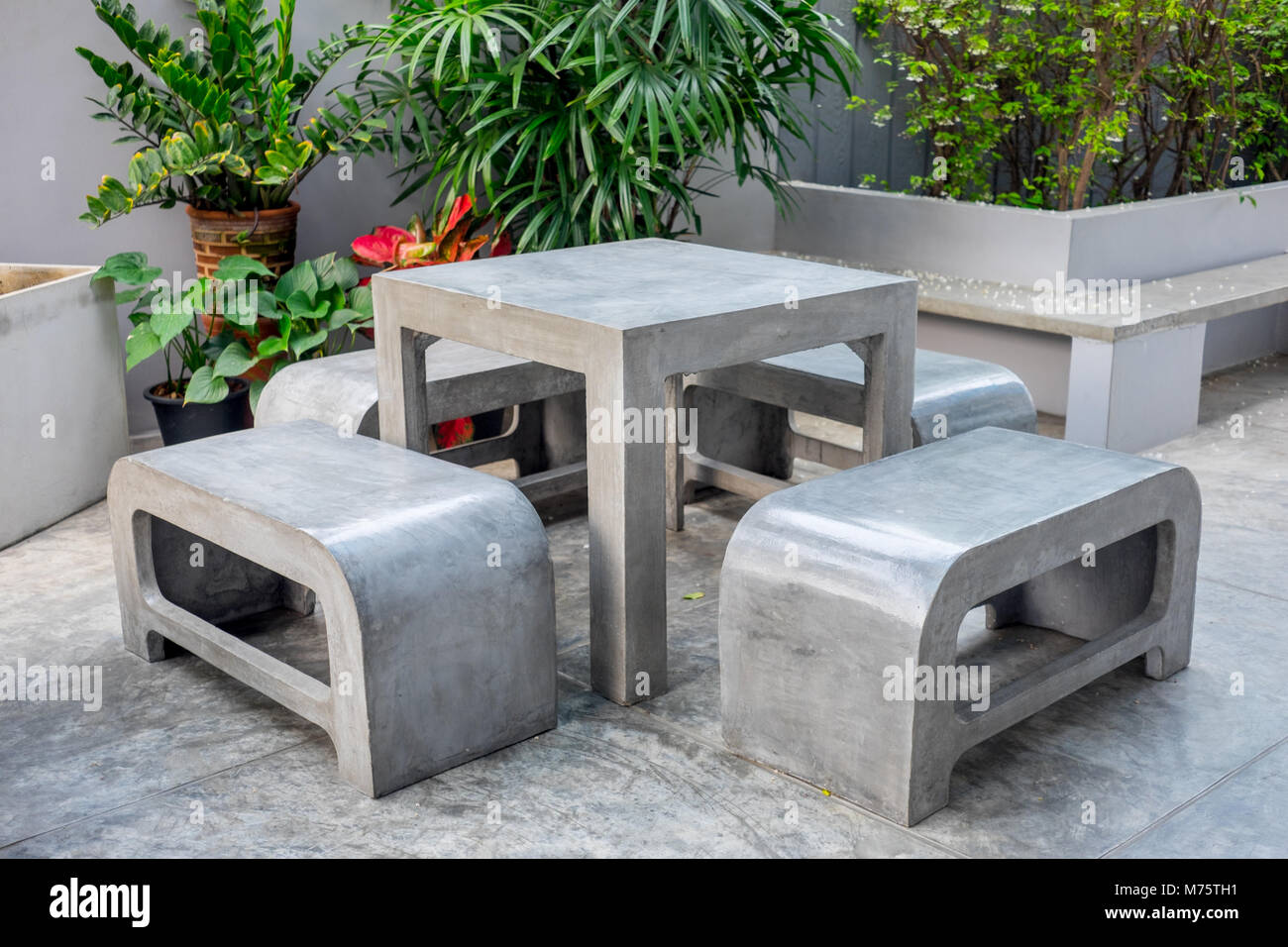Concrete outdoor furniture set in the small garden including on table and four benches & Concrete outdoor furniture set in the small garden including on ...