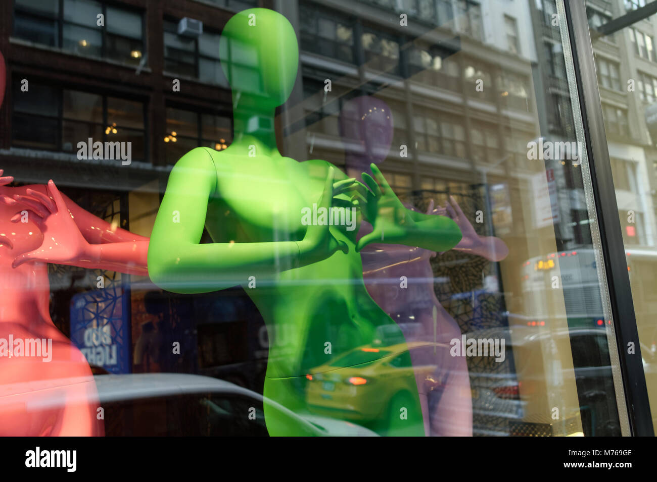 Bare bal colorful mannequins on a window display with reflection. - Stock Image