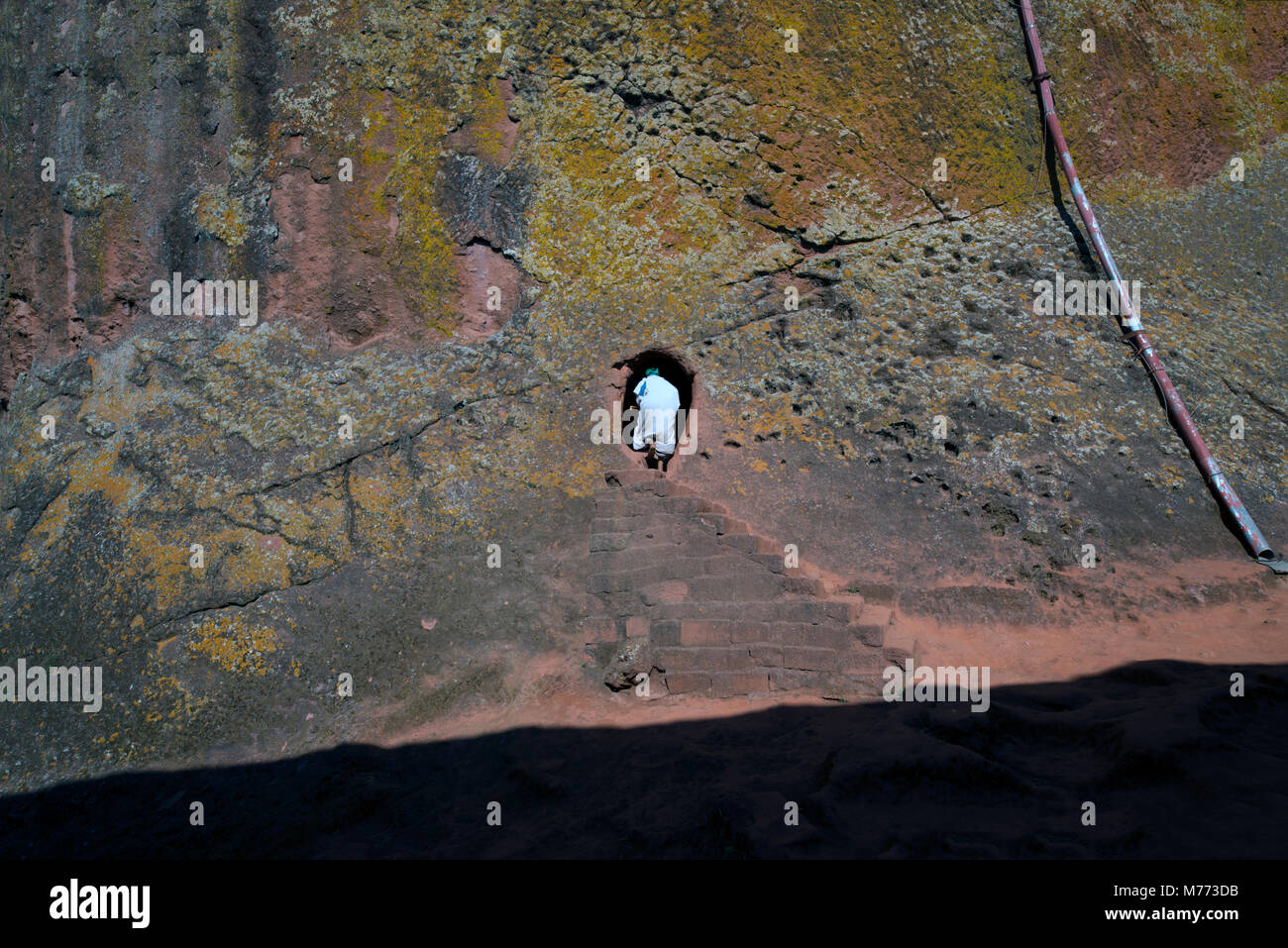 A worshipper entering a church that was carved from solid rock. Lalibela, Ethiopia. - Stock Image