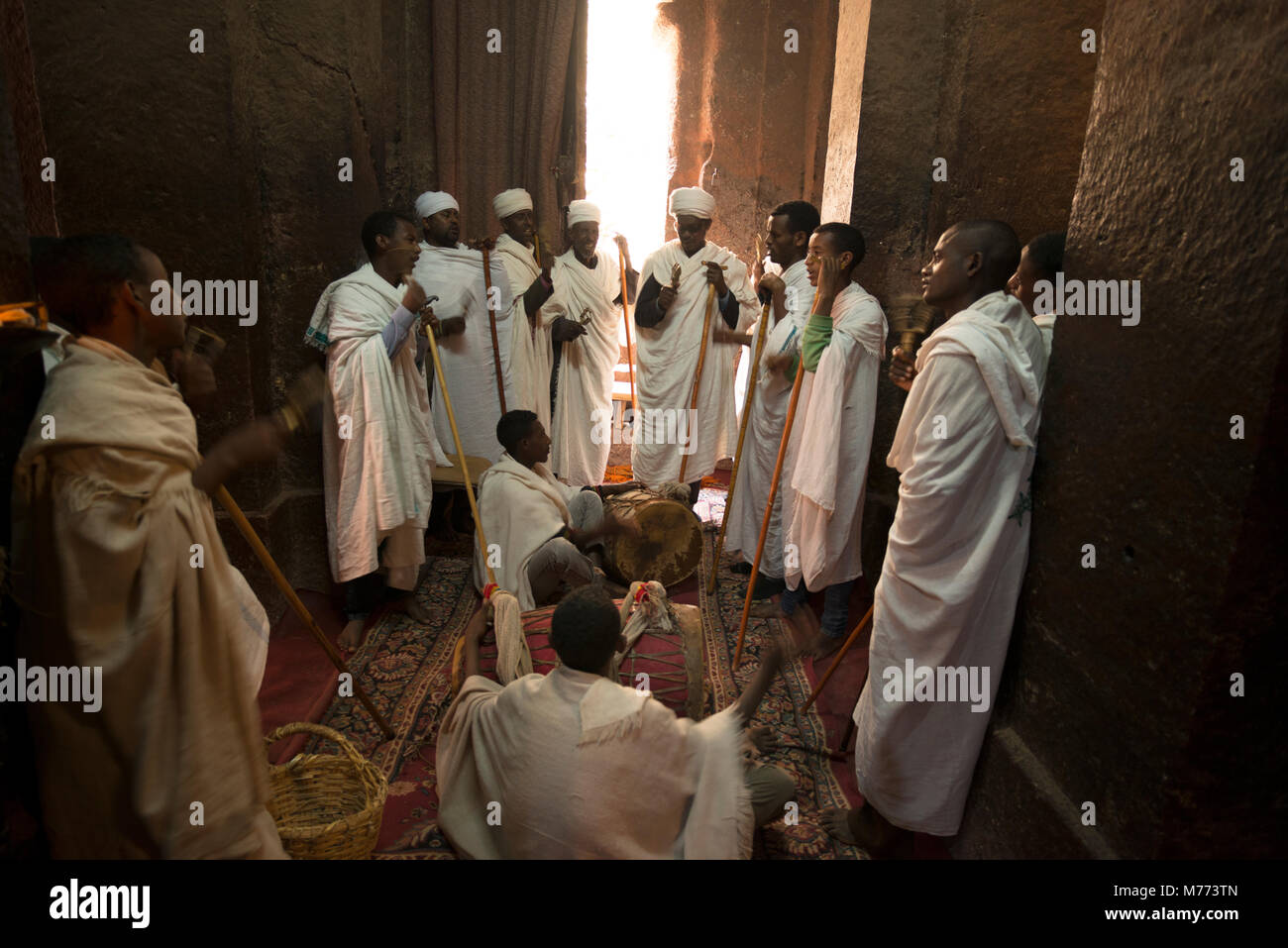 Priests wearing white robes are chanting to the beat of a drum inside a rock-hewn church in Lalibela, Ethiopia. - Stock Image