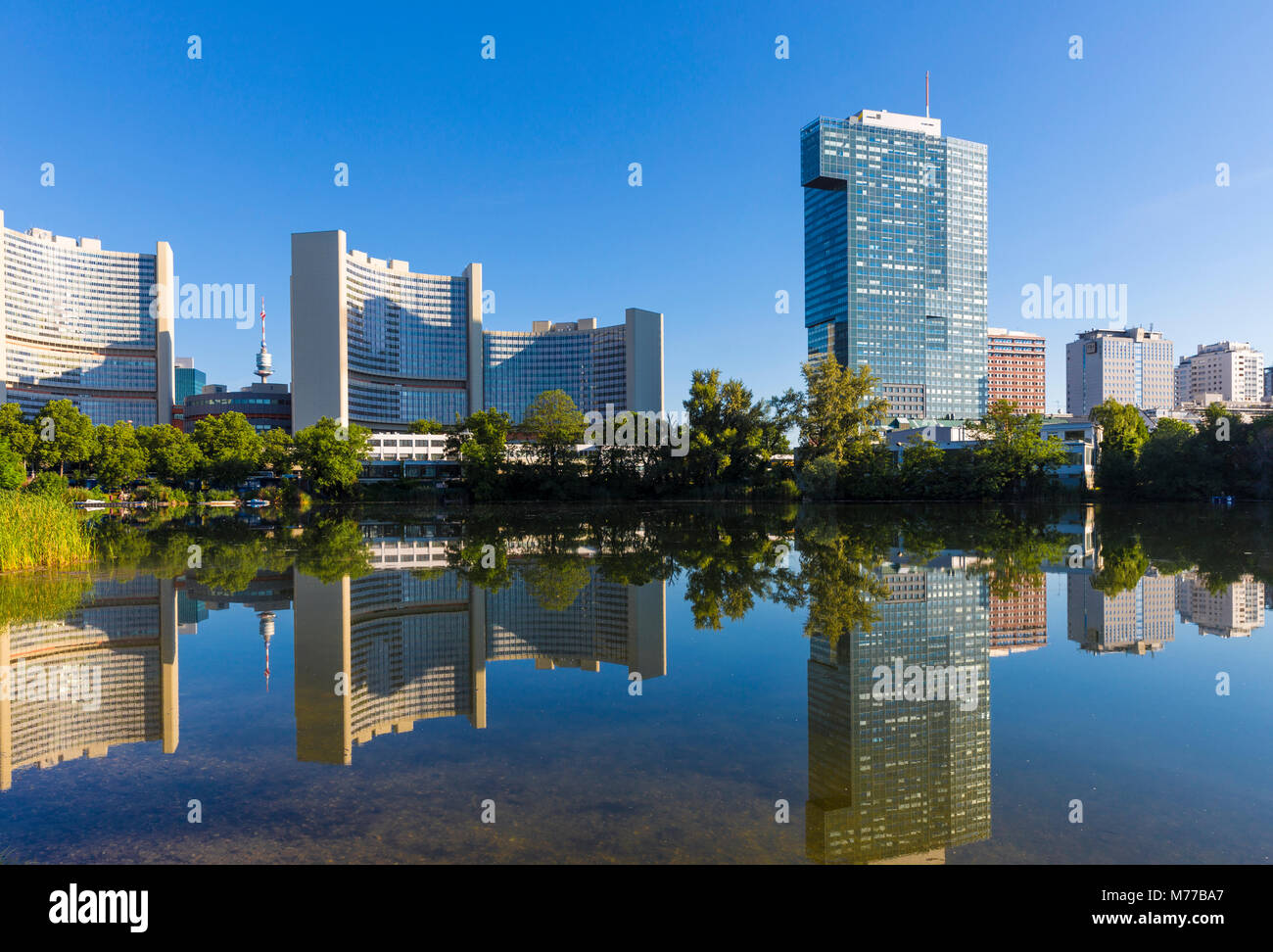 United Nations buildings reflected in lake, UNO City, Vienna, Austria, Europe - Stock Image