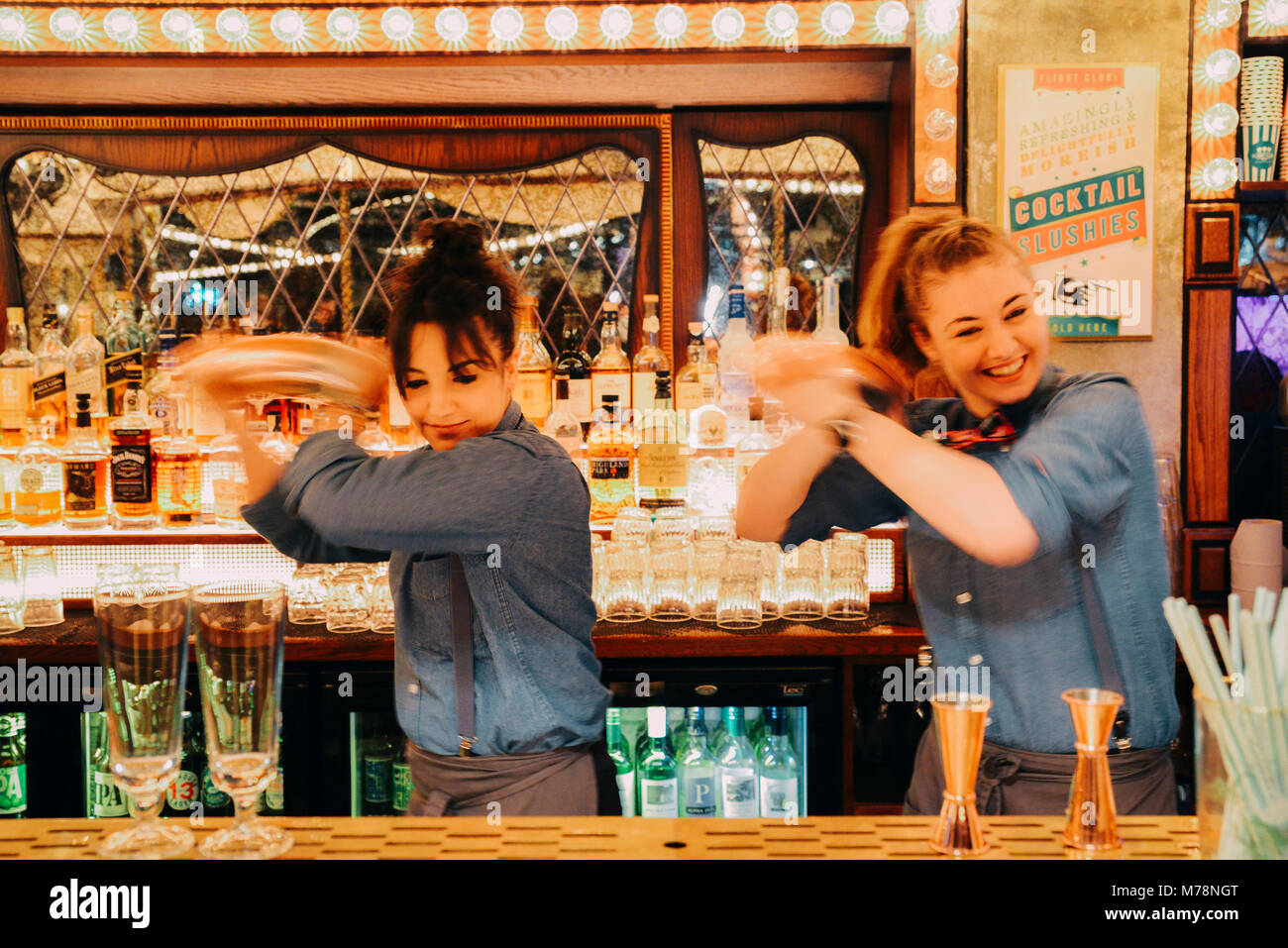 Two female bartenders mix drinks at a bright carnival fair style bar counter at the Flight Cub, a vintage social Stock Photo