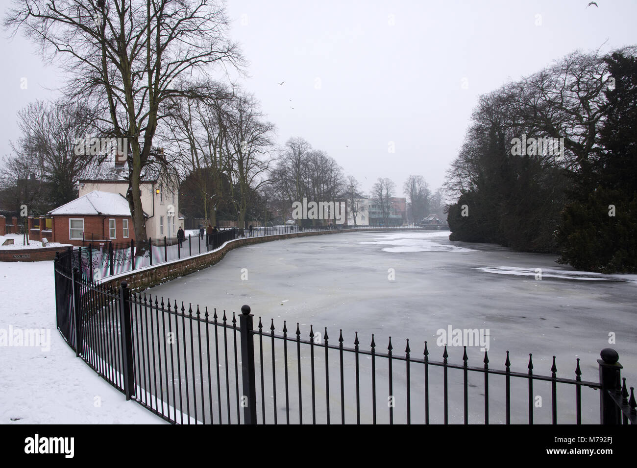 Iron railings Minster Walk and frozen Minster Pool in unseasonal cold weather of 3rd March 2018 in Lichfield Staffordshire - Stock Image