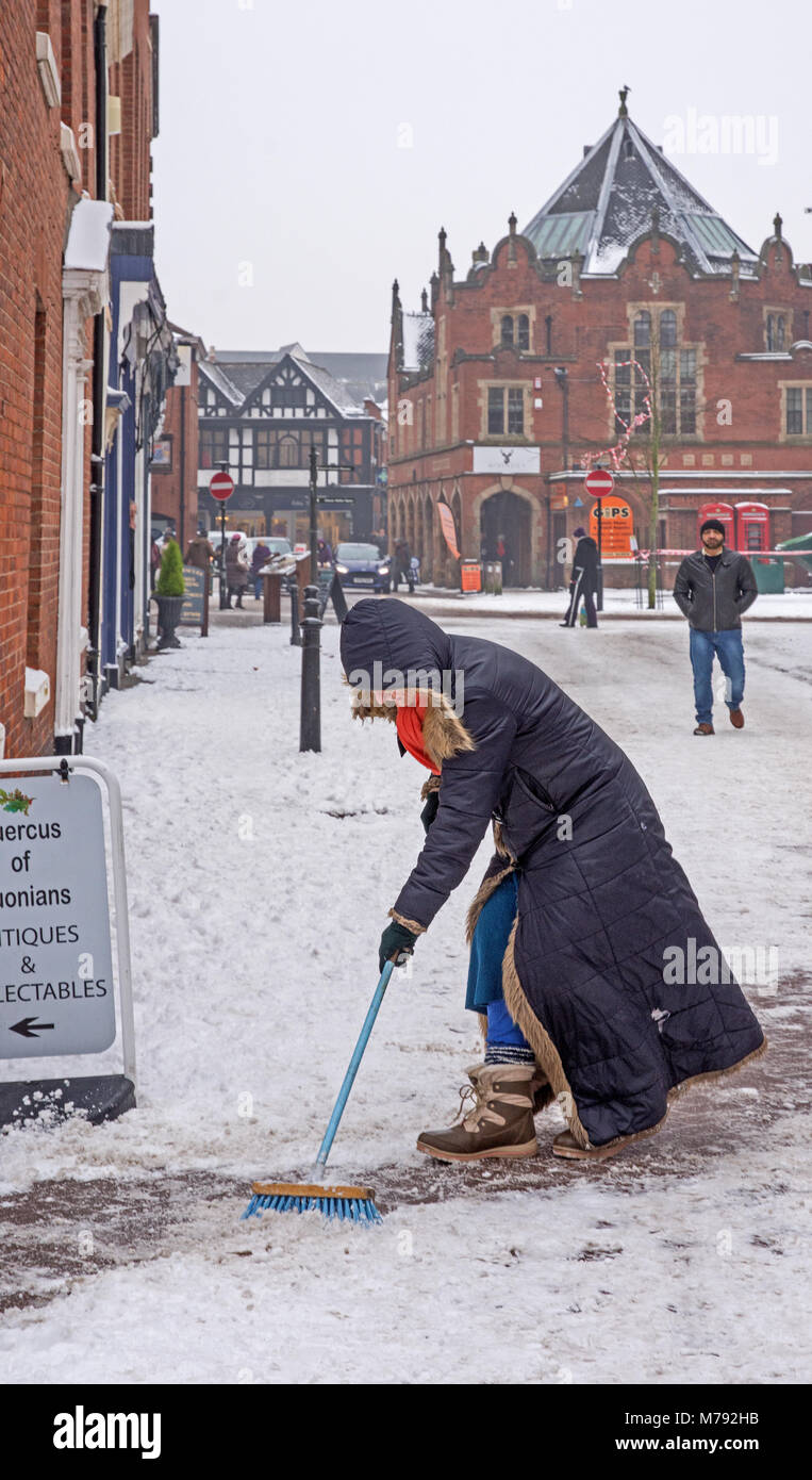 Lady with black coat and hood clearing a path through the snow with a brush or broom in Dam Street Lichfield Staffordshire - Stock Image