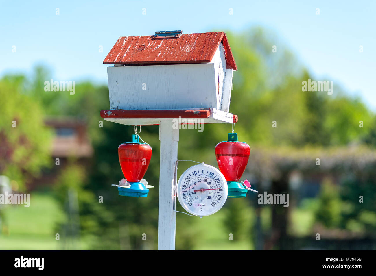 Thermometer with bird house and hummingbird feeders - Stock Image