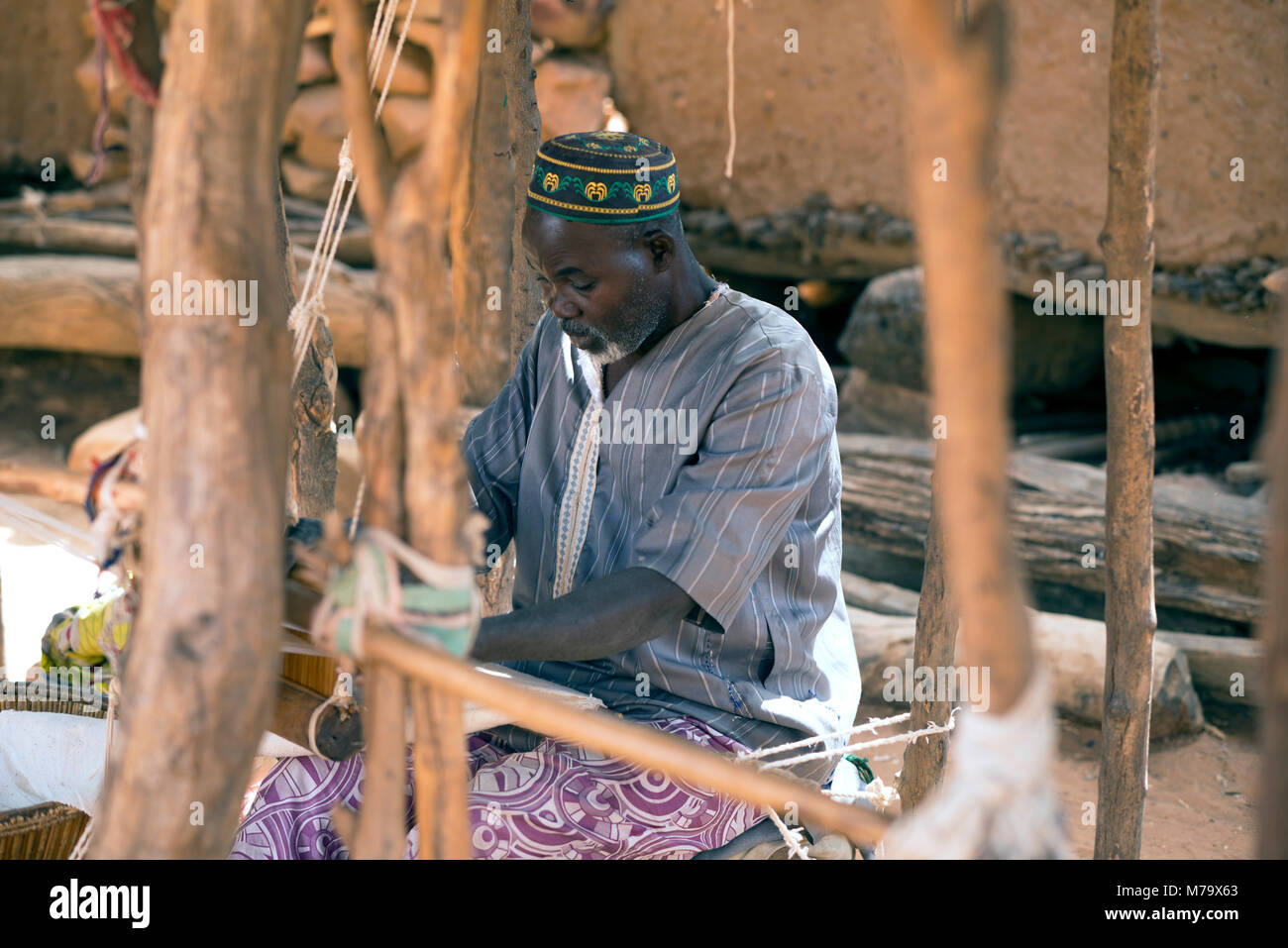 A Dogon man makes his living from weaving cloth. Mali, West Africa. - Stock Image