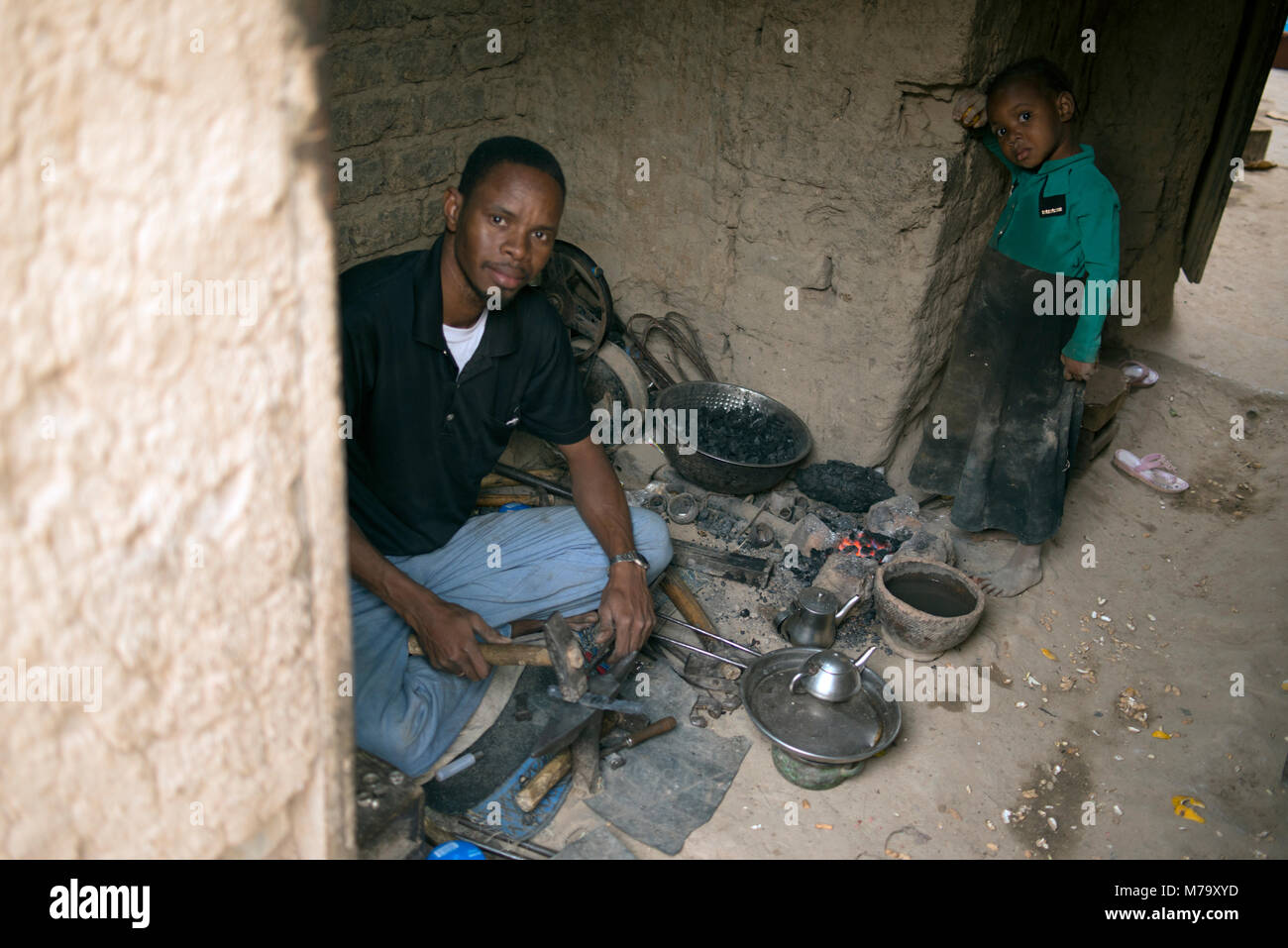 A blacksmith and his son in their village house. Mopti Region, Mali, West Africa. - Stock Image