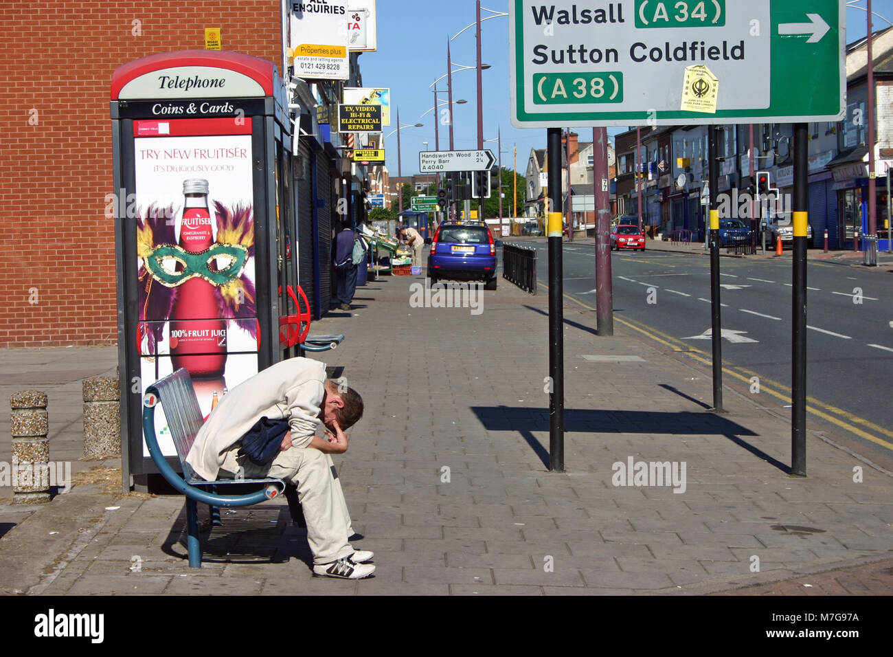 Depressed white man sitting on a bench, Soho Road, Handsworth, Birmingham - Stock Image