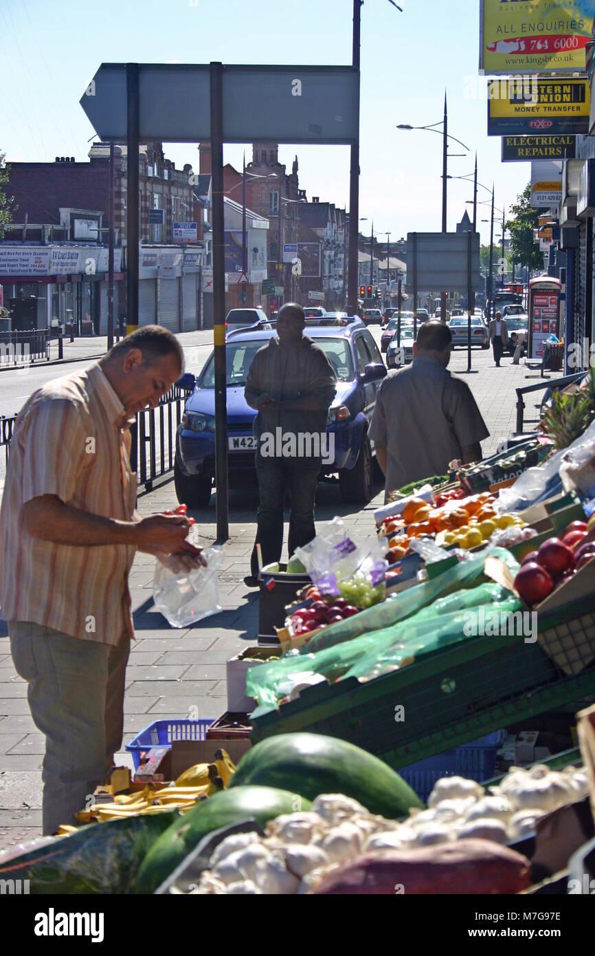 Asian man inspecting grocery display on the street, Soho Road, Birmingham - Stock Image