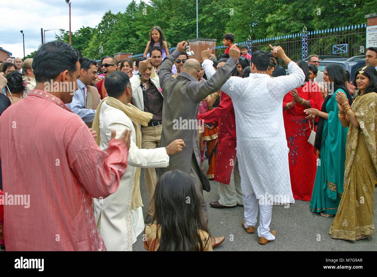 Men dancing at Asian wedding, at Villa Park, Birmingham - Stock Image