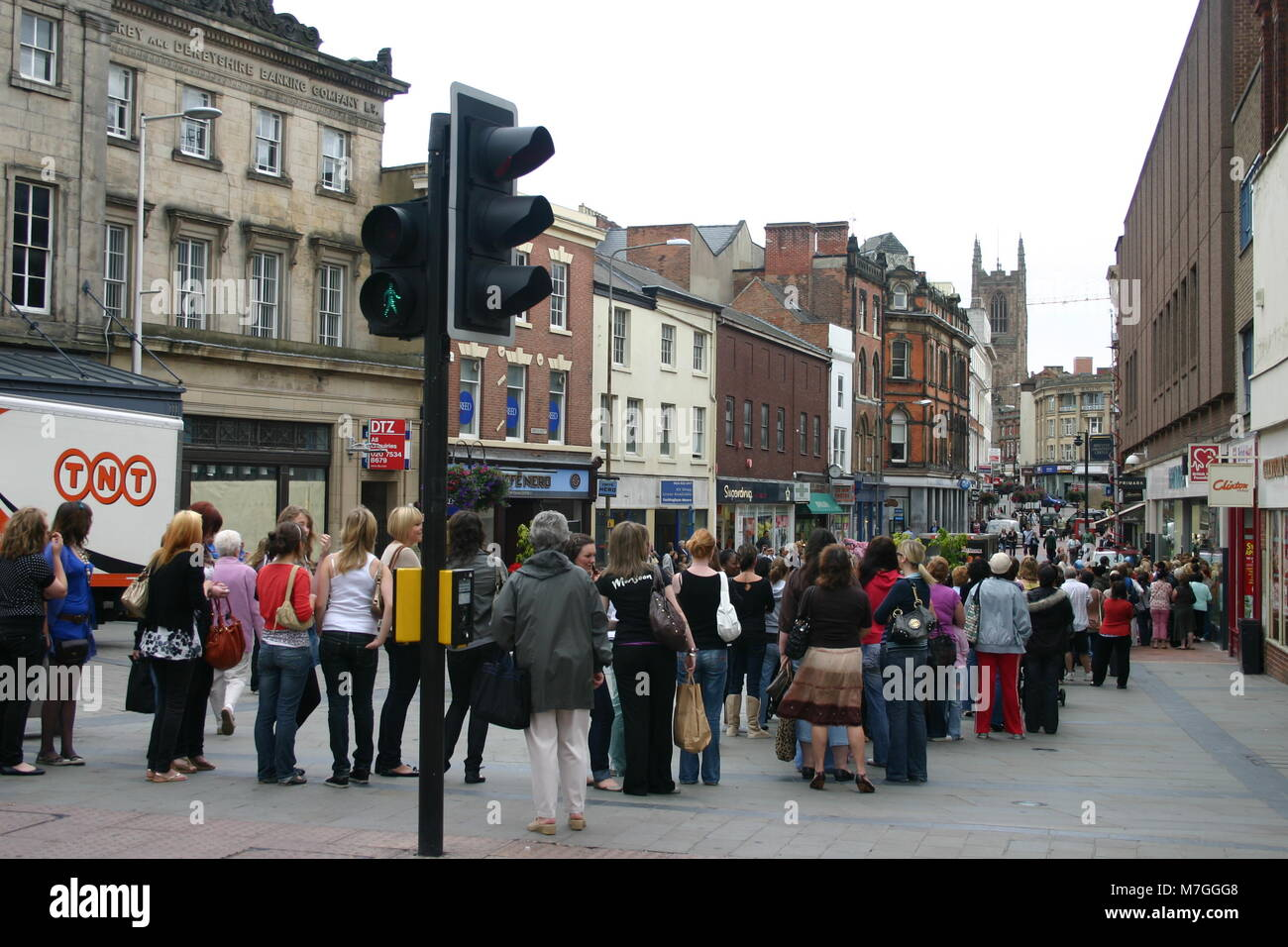 The sales, with customers forming a long queue outside a retail store Derby, UK - Stock Image
